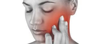 woman touching cheek in pain