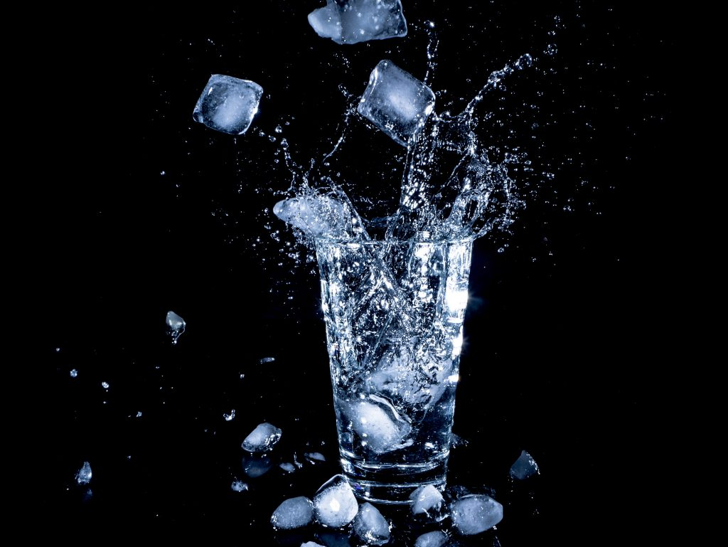water splashing into glass of ice