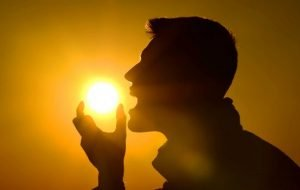 man in silhouette eating sun