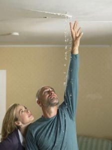 man and woman standing under leaking ceiling