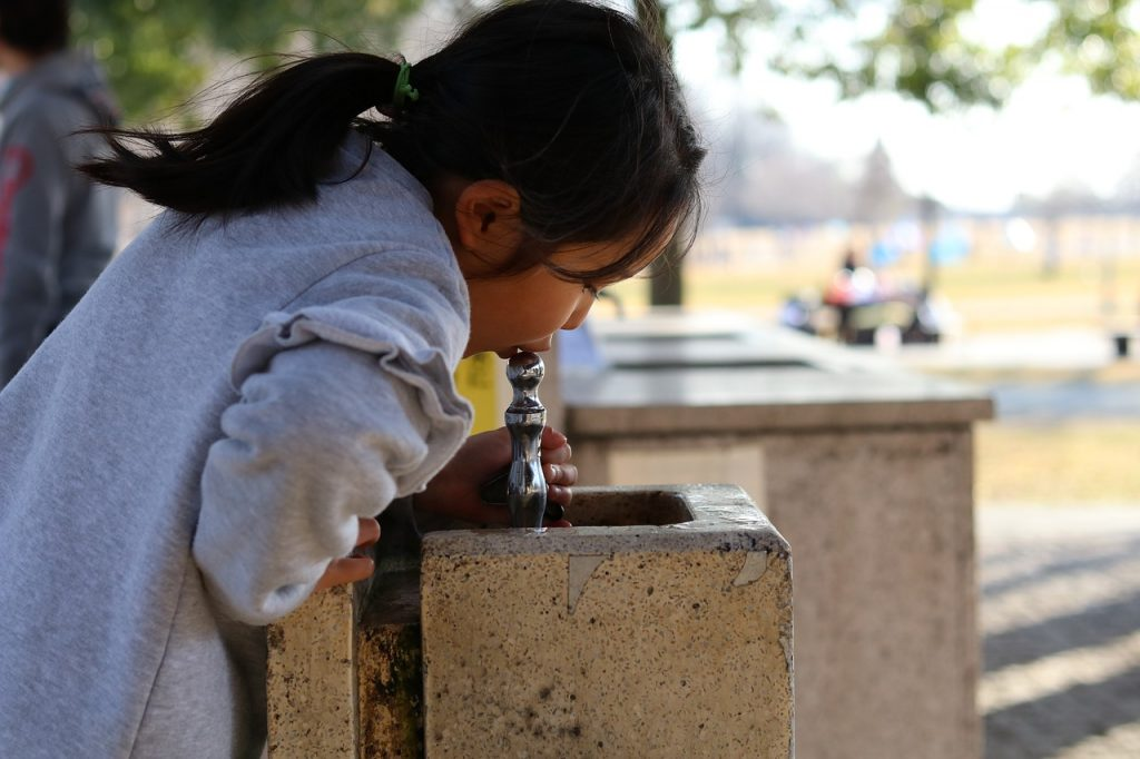child drinking from water fountain