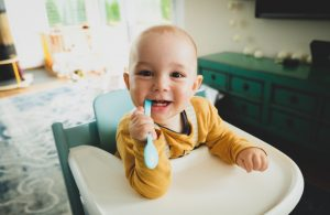 baby in high chair with spoon