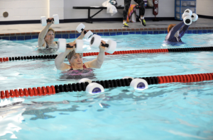 group taking exercise class in pool