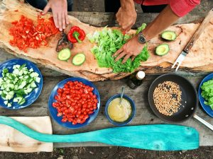 people preparing a vegetable and nut salad
