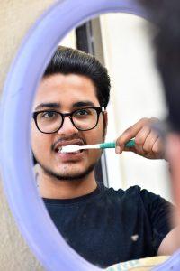 man brushing teeth in mirror