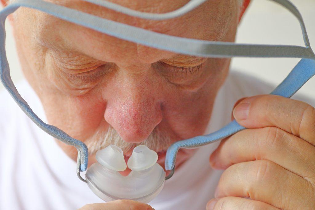 older man with CPAP headgear